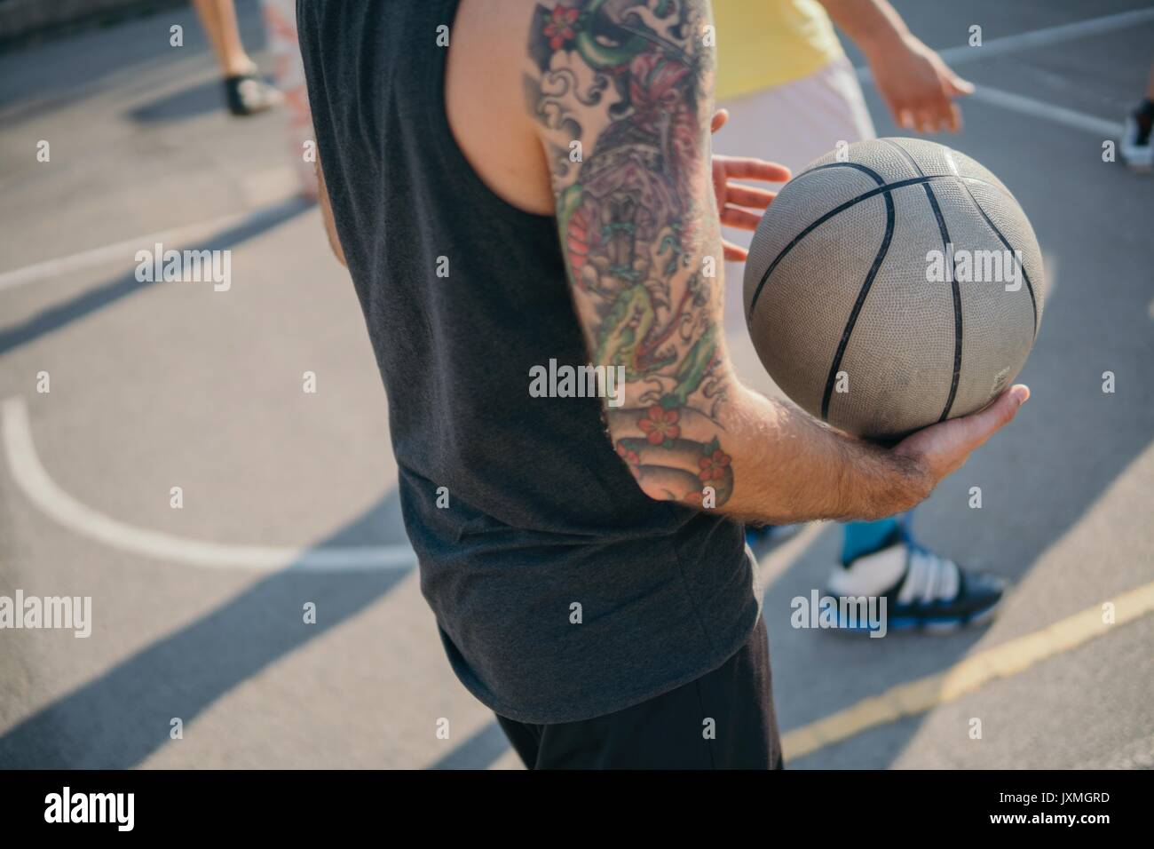 Cropped view of friends on basketball court holding basketball - Stock Image