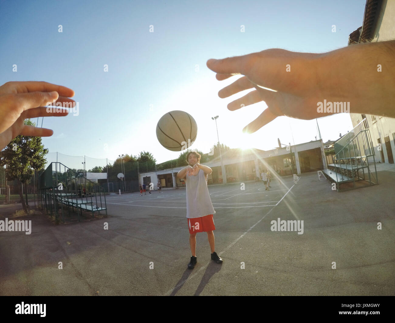 Point of view image of man throwing basketball at teammate - Stock Image