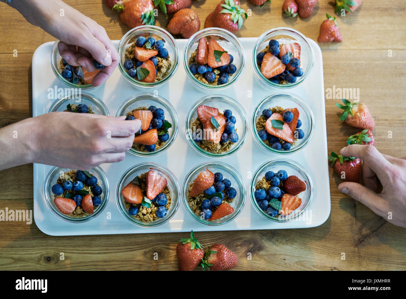 Two chefs preparing berry desserts, overhead view - Stock Image