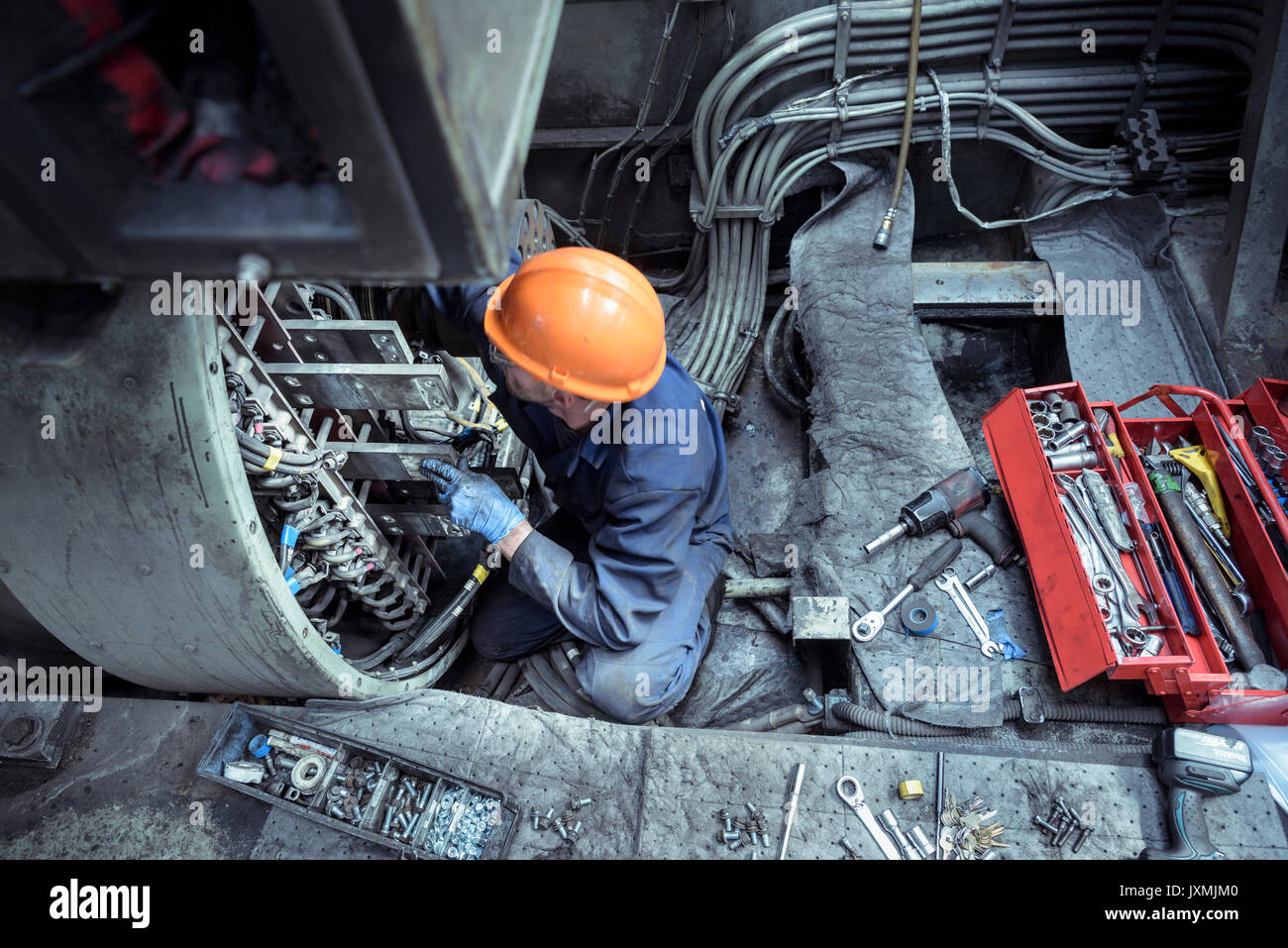 Locomotive engineer working on locomotive engine in train works - Stock Image