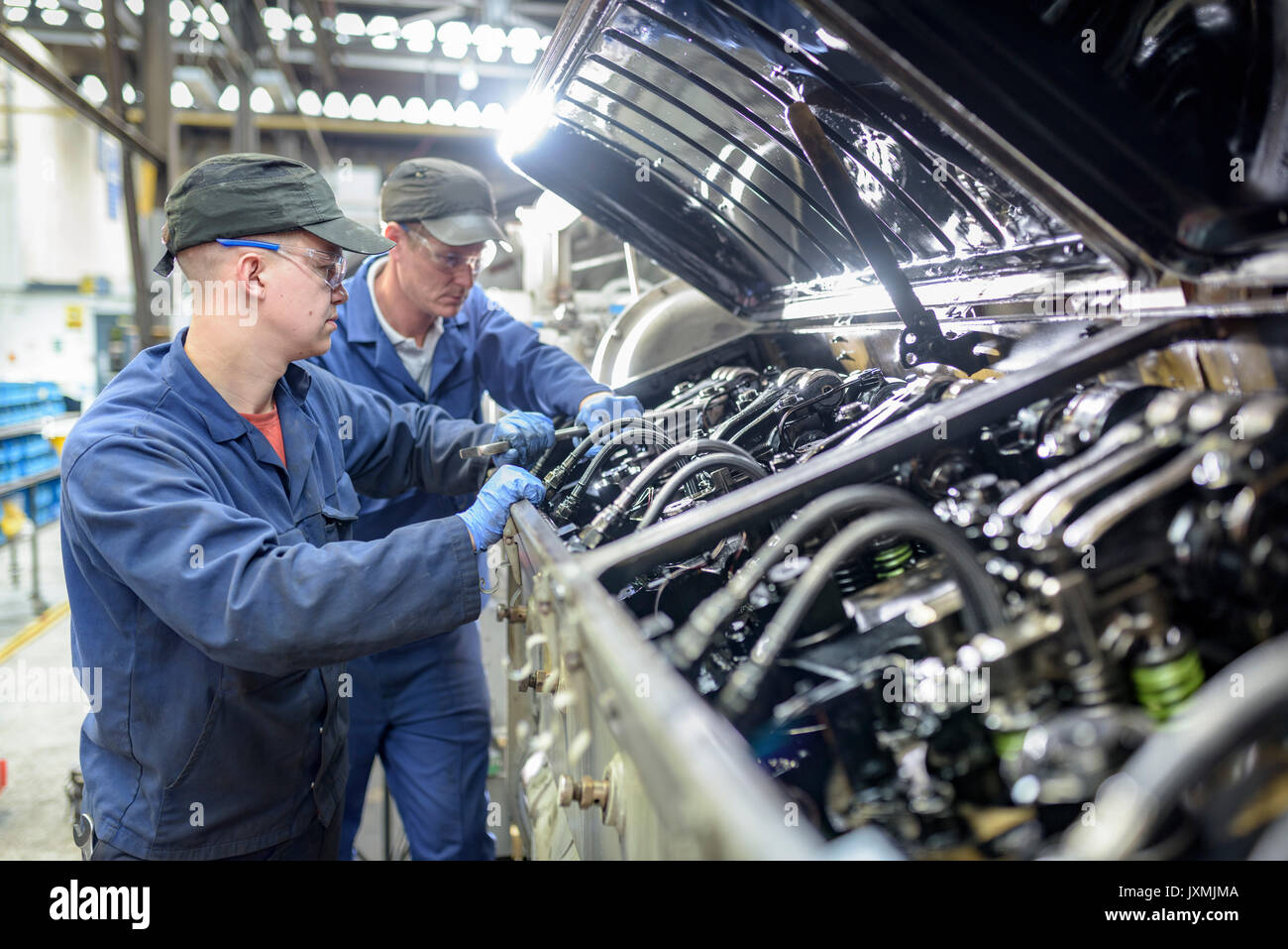 Engineer and apprentice working on locomotive engine in train works - Stock Image
