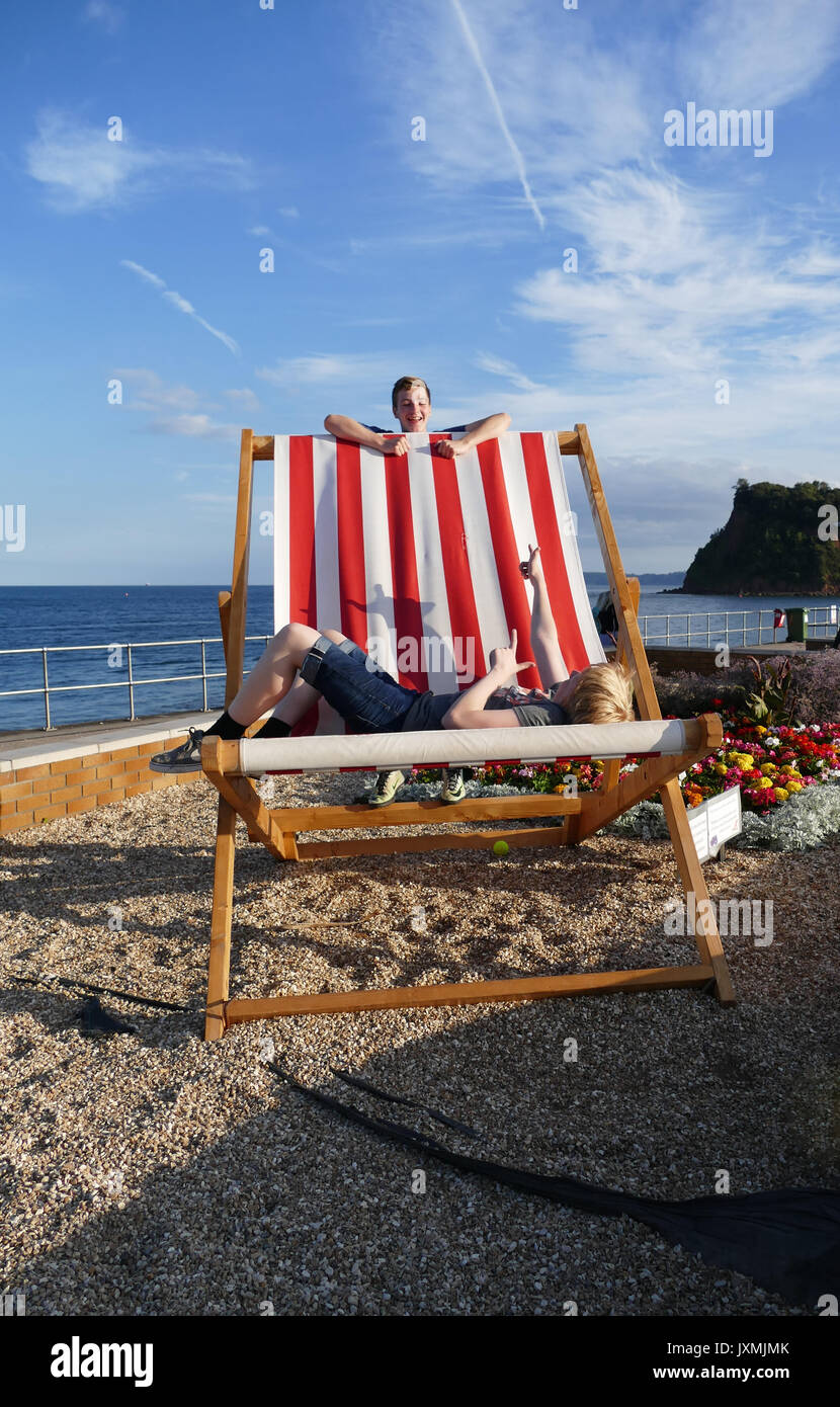 Two boys playing on a giant deckchair in Teignmouth Devon U.K. - Stock Image