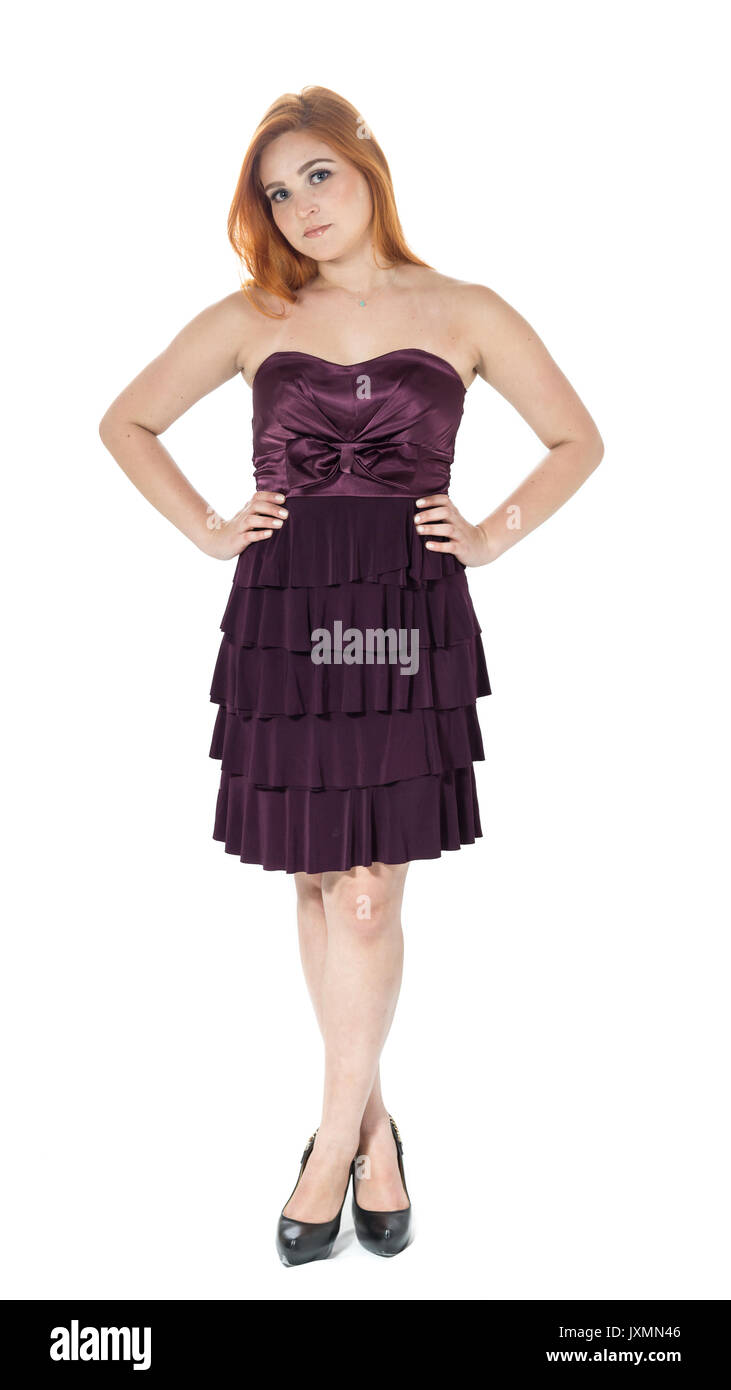Full-length portrait of young woman. The legs are crossed and hands on the hips. Redheaded teenager wearing dark purple strapless dress. Isolated - Stock Image
