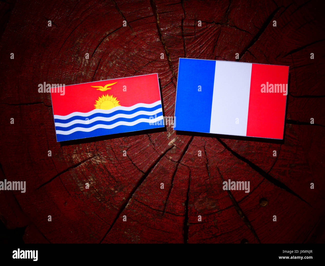Kiribati flag with French flag on a tree stump isolated Stock Photo