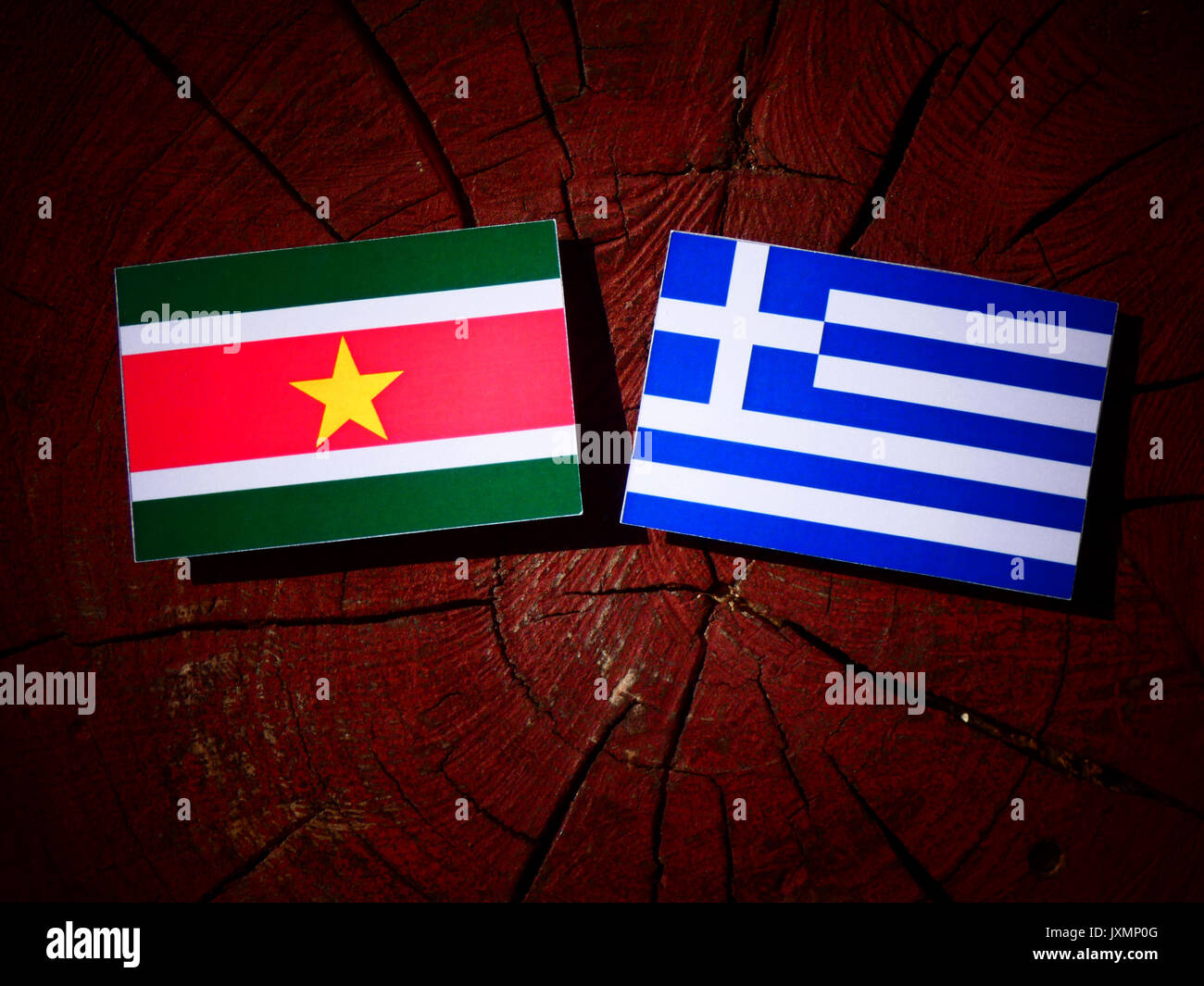 Suriname flag with Greek flag on a tree stump isolated - Stock Image
