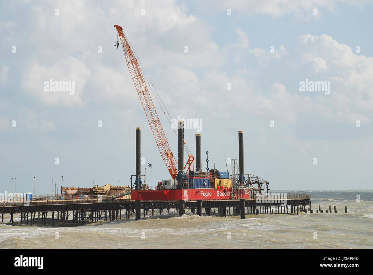 A crane on a jack-up-barge being used to demolish burnt out building remains on the Victorian pier in Hastings, England on November 9, 2014. - Stock Image