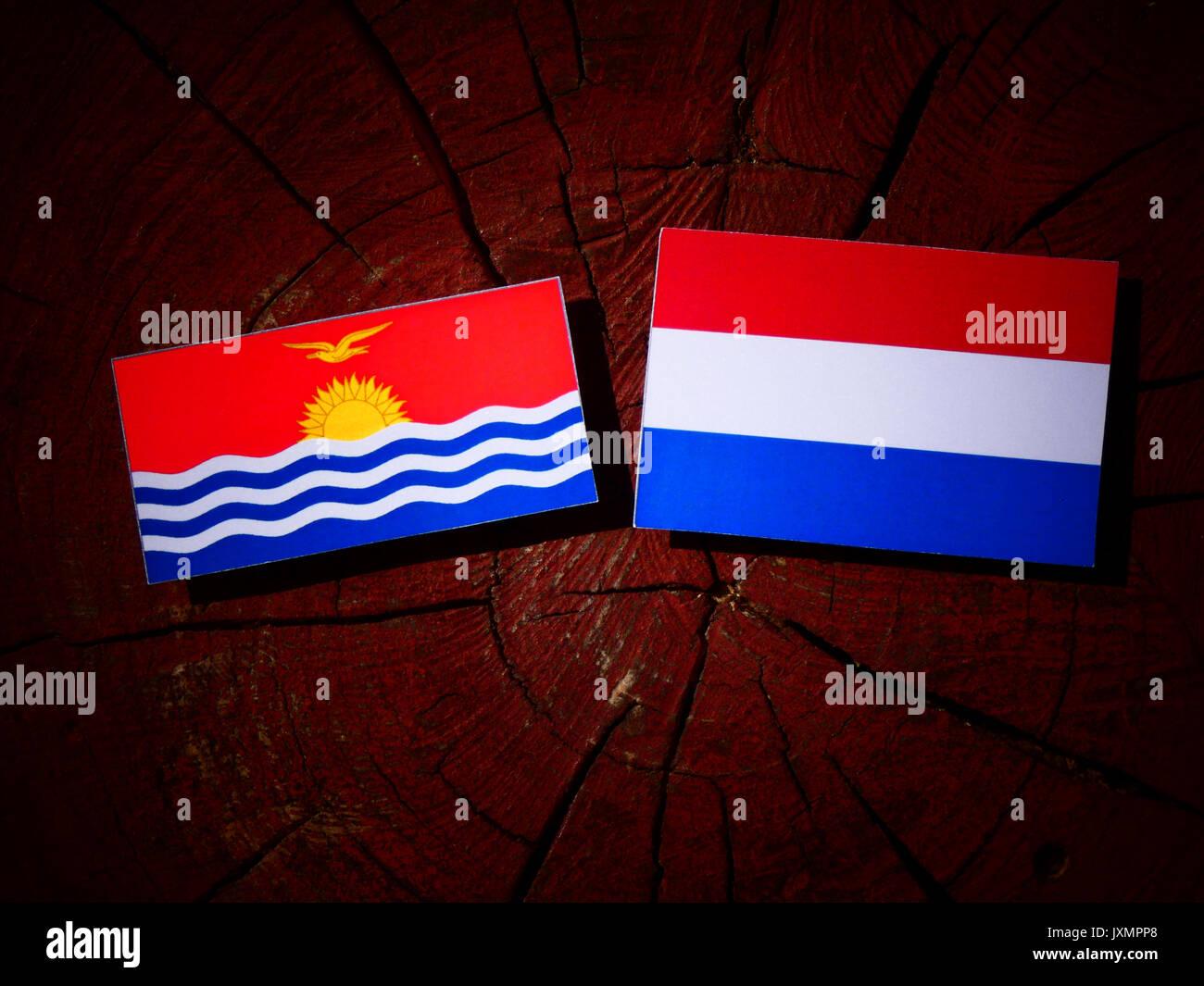 Kiribati flag with Dutch flag on a tree stump isolated - Stock Image