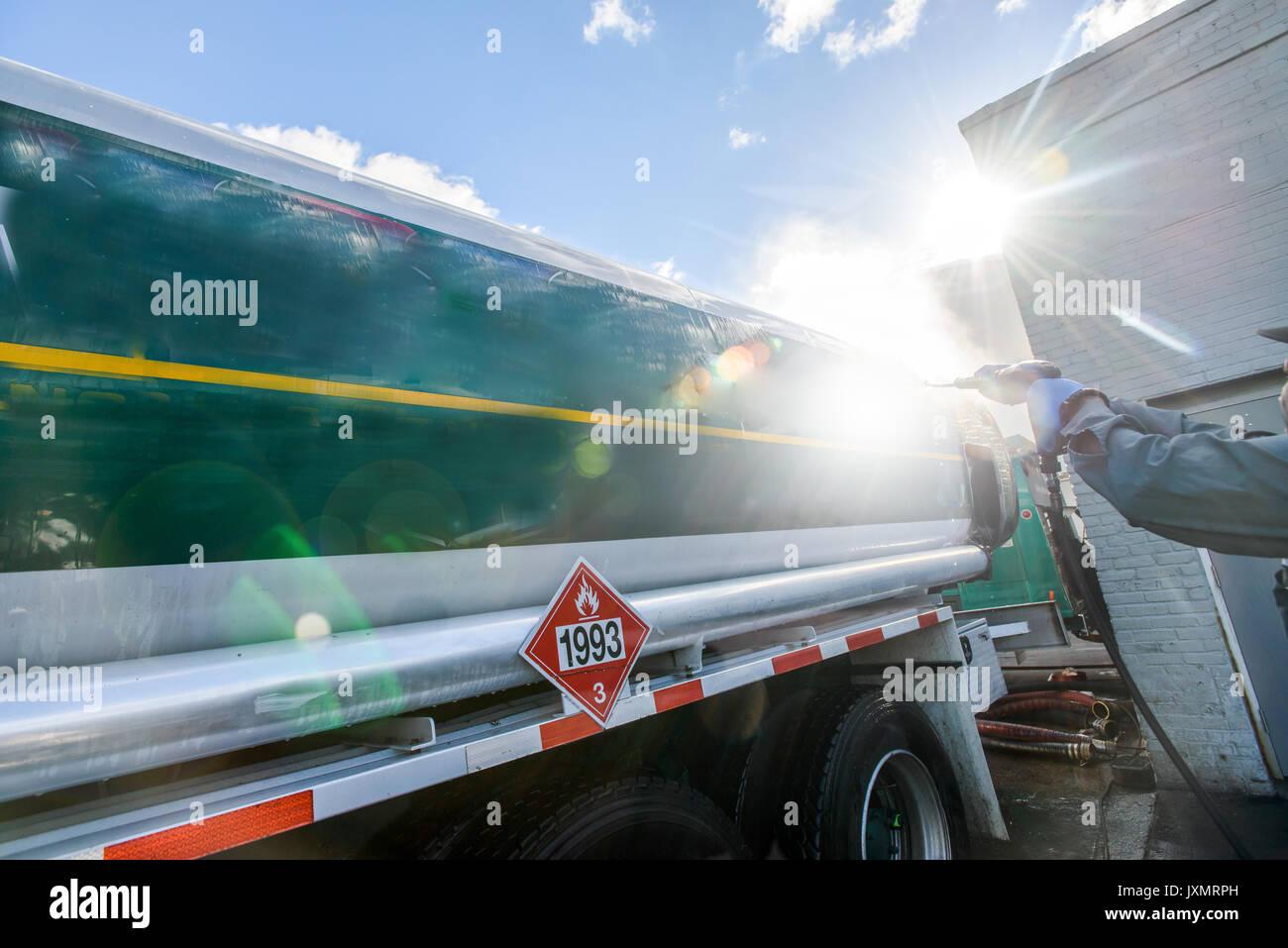 Worker pressure hosing biofuel oil tanker at sunlit biofuel plant - Stock Image
