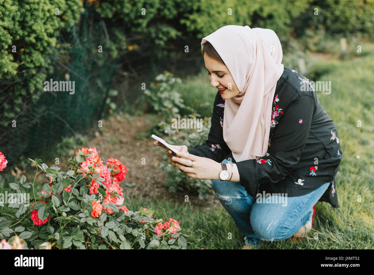 Young woman wearing hijab photographing flowers with smartphone - Stock Image