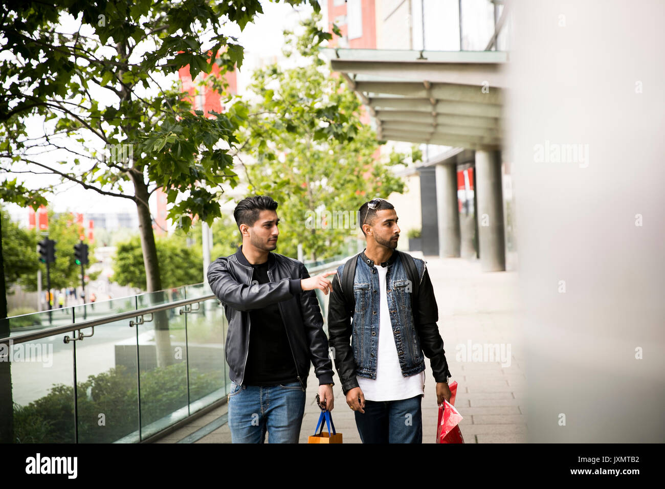 Two young men, walking past shops, pointing in shop window Stock Photo