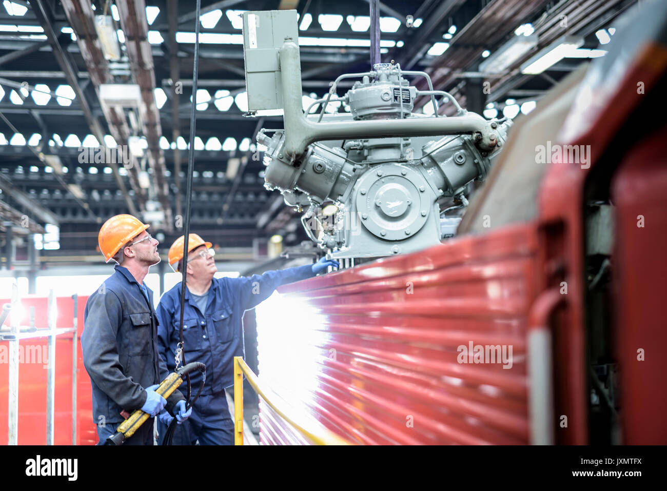 Locomotive engineers craning engine parts in train works - Stock Image