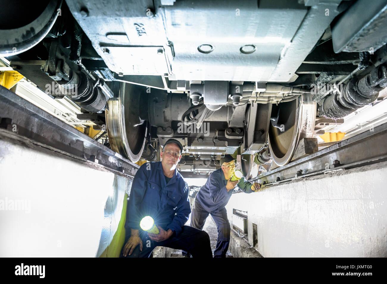 Locomotive engineers inspecting underside of locomotive in train works - Stock Image
