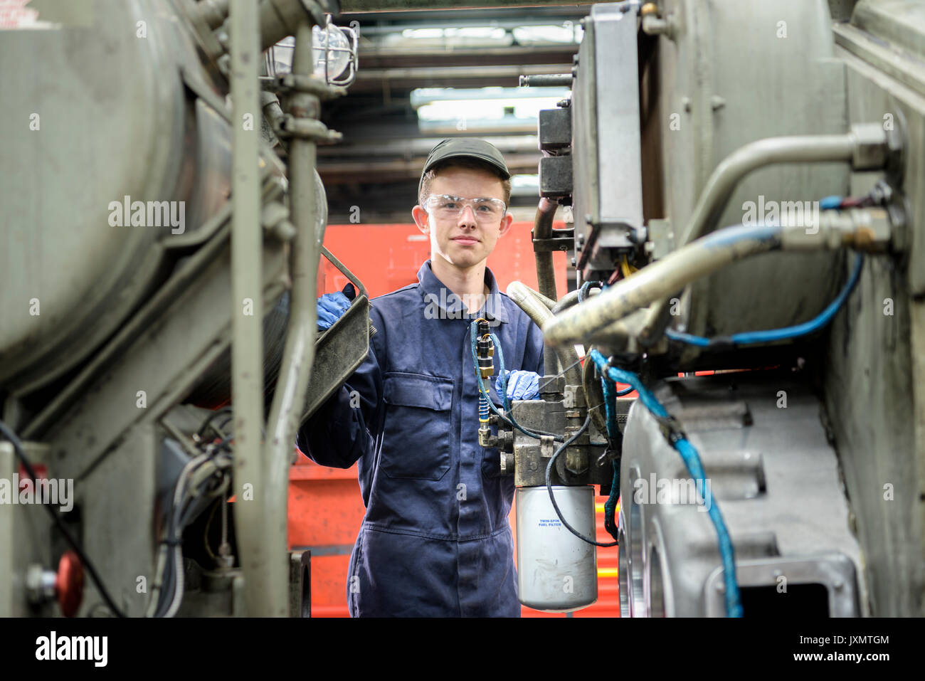 Portrait of young apprentice locomotive engineer in train works - Stock Image