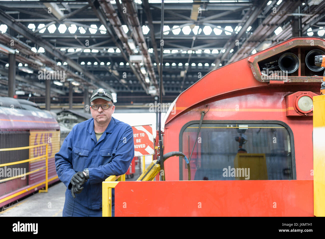 Portrait of locomotive engineer working in train works - Stock Image
