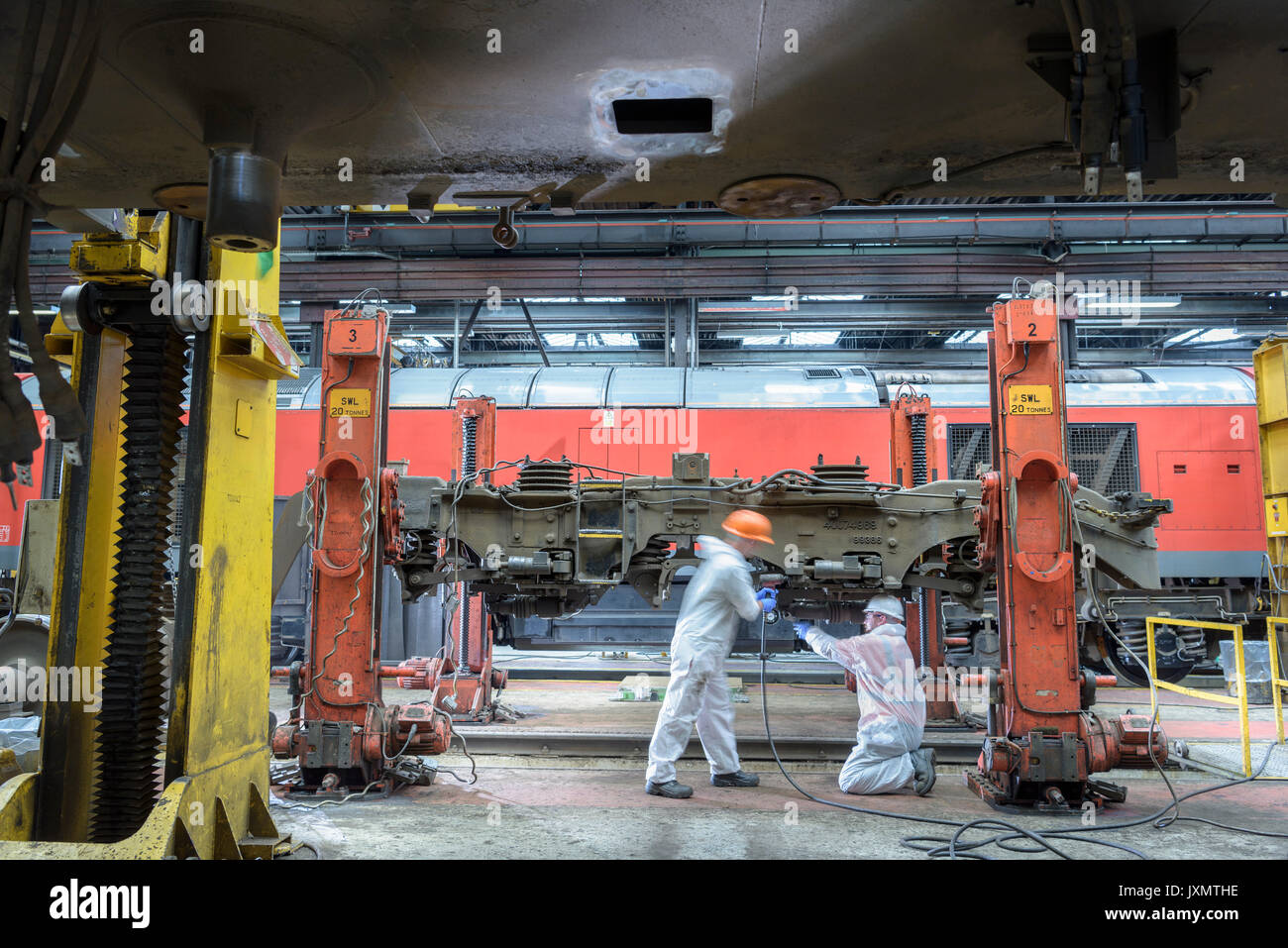 Locomotive engineers working on locomotive in train works - Stock Image