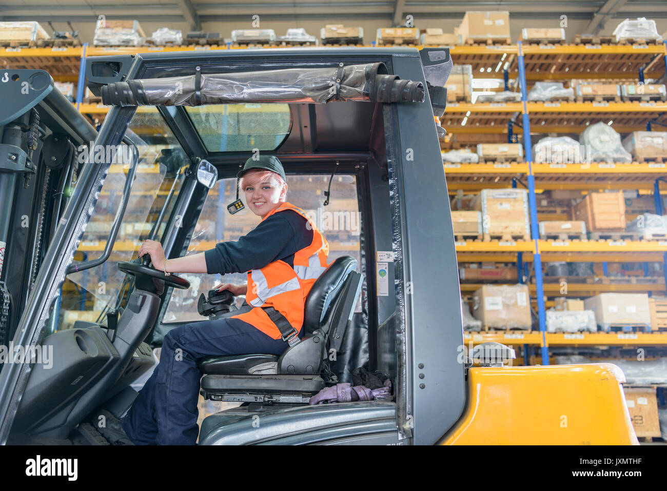 Portrait of female forklift truck driver in train works warehouse - Stock Image