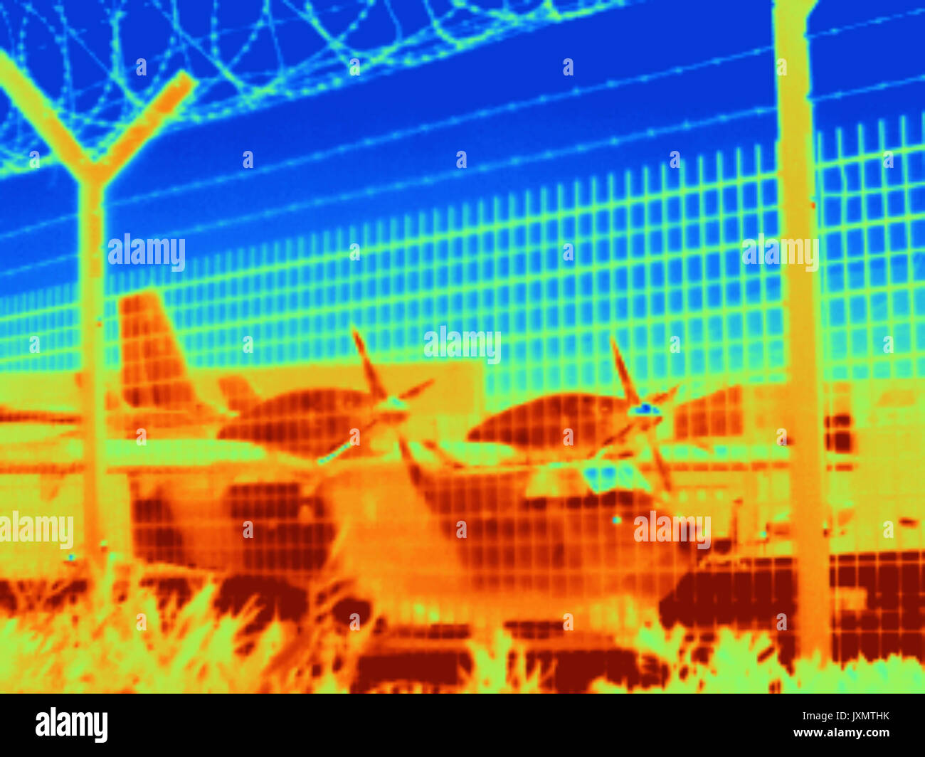 Thermal image of aeroplane seen through wire fence - Stock Image