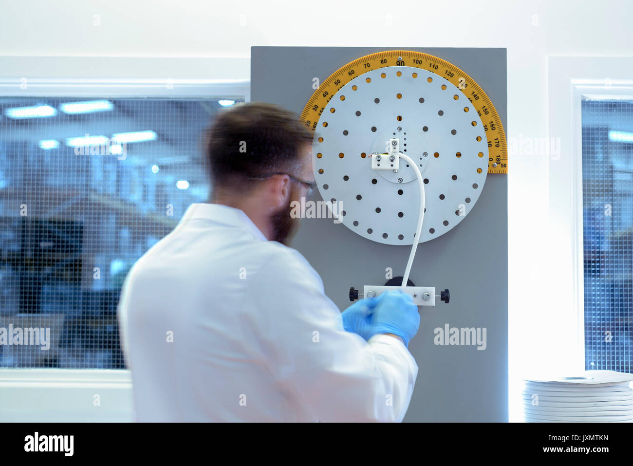 Scientist using cable bending test equipment to test electrical cable in electrical cable laboratory - Stock Image