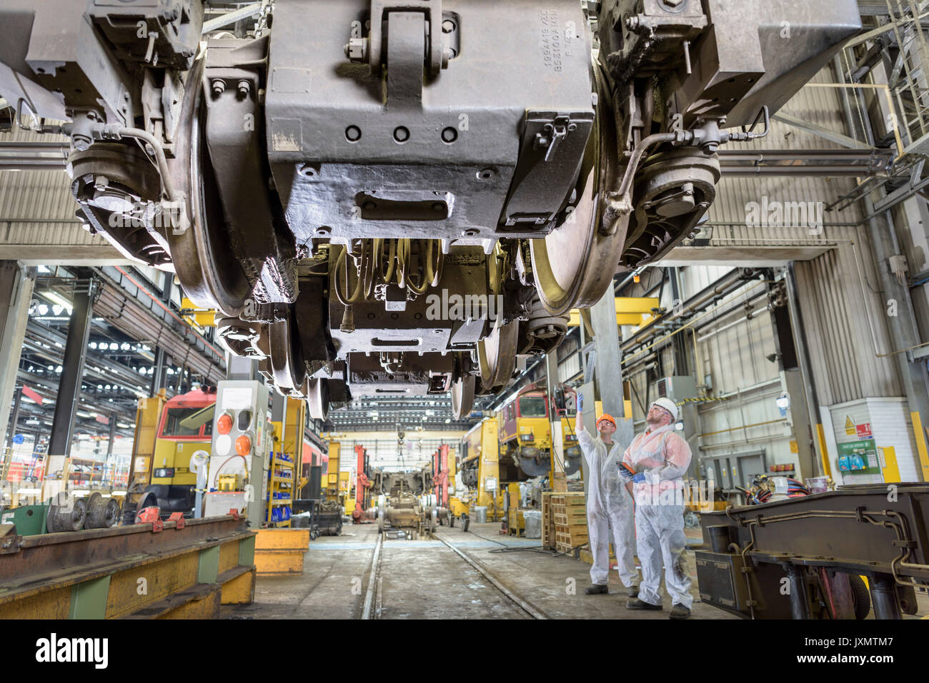 Locomotive engineers working on locomotive in train works - Stock Image