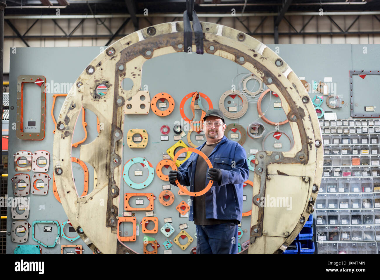 Portrait of locomotive engineer picking gaskets and seals in train works - Stock Image