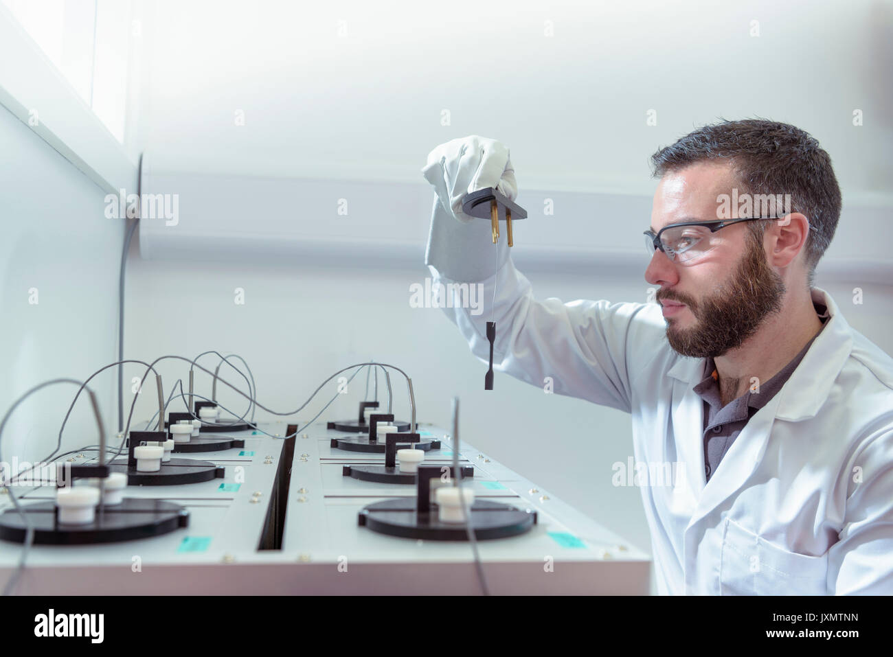 Scientist age testing electrical cable in electrical cable laboratory - Stock Image