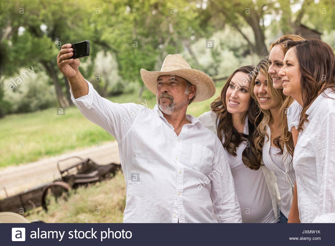 Mature man taking smartphone selfie with women on ranch, Bridger, Montana, USA - Stock Image