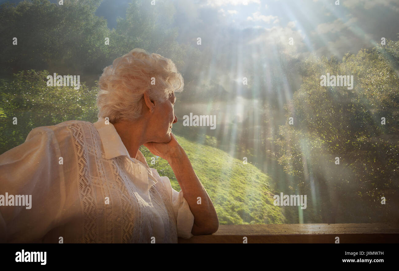 Senior woman looking at relaxing rural scene, from condo window - Stock Image