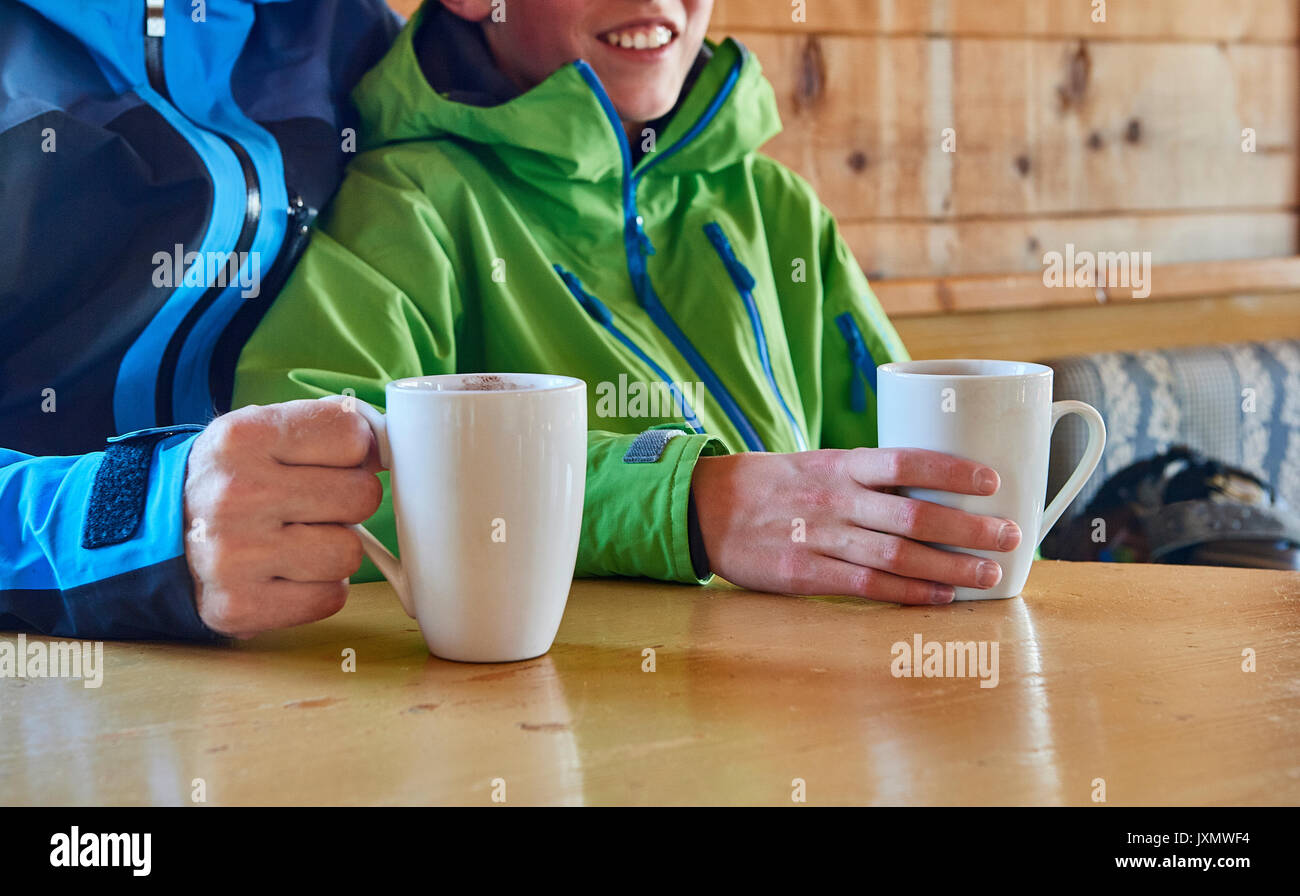 Father and son taking coffee break in log cabin, Hintertux, Tirol, Austria - Stock Image