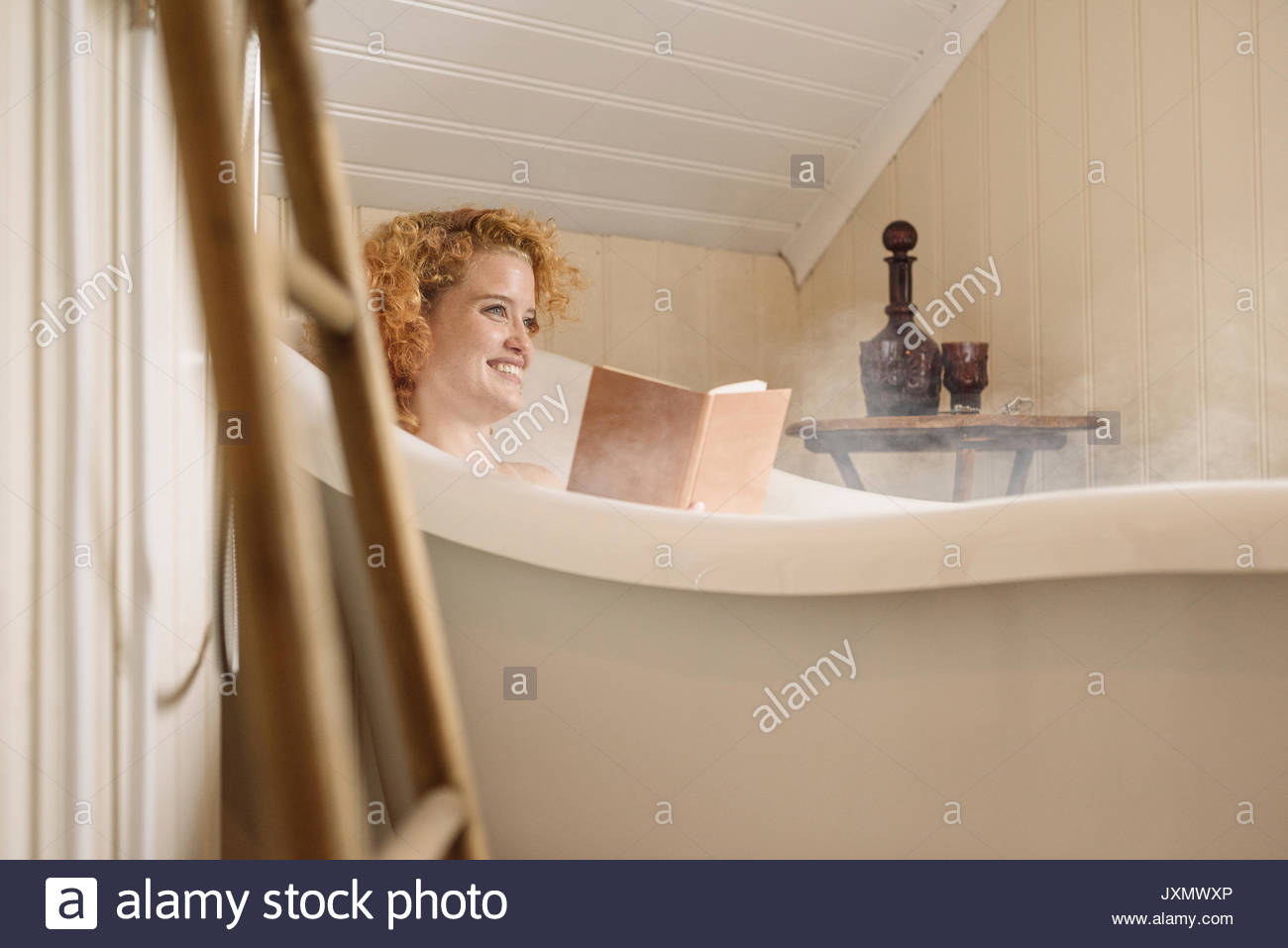 Woman in bathtub reading book Stock Photo: 154123390 - Alamy