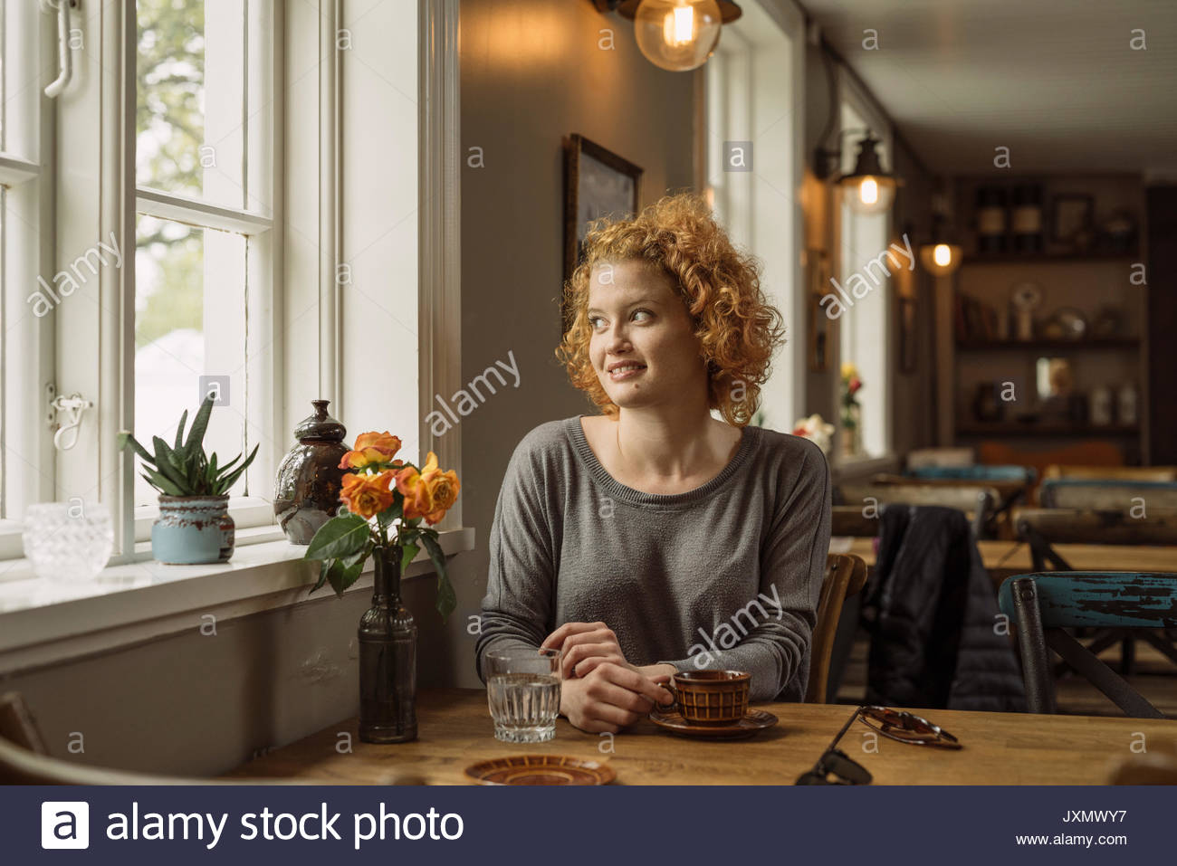 Woman in cafe looking away out of window smiling - Stock Image