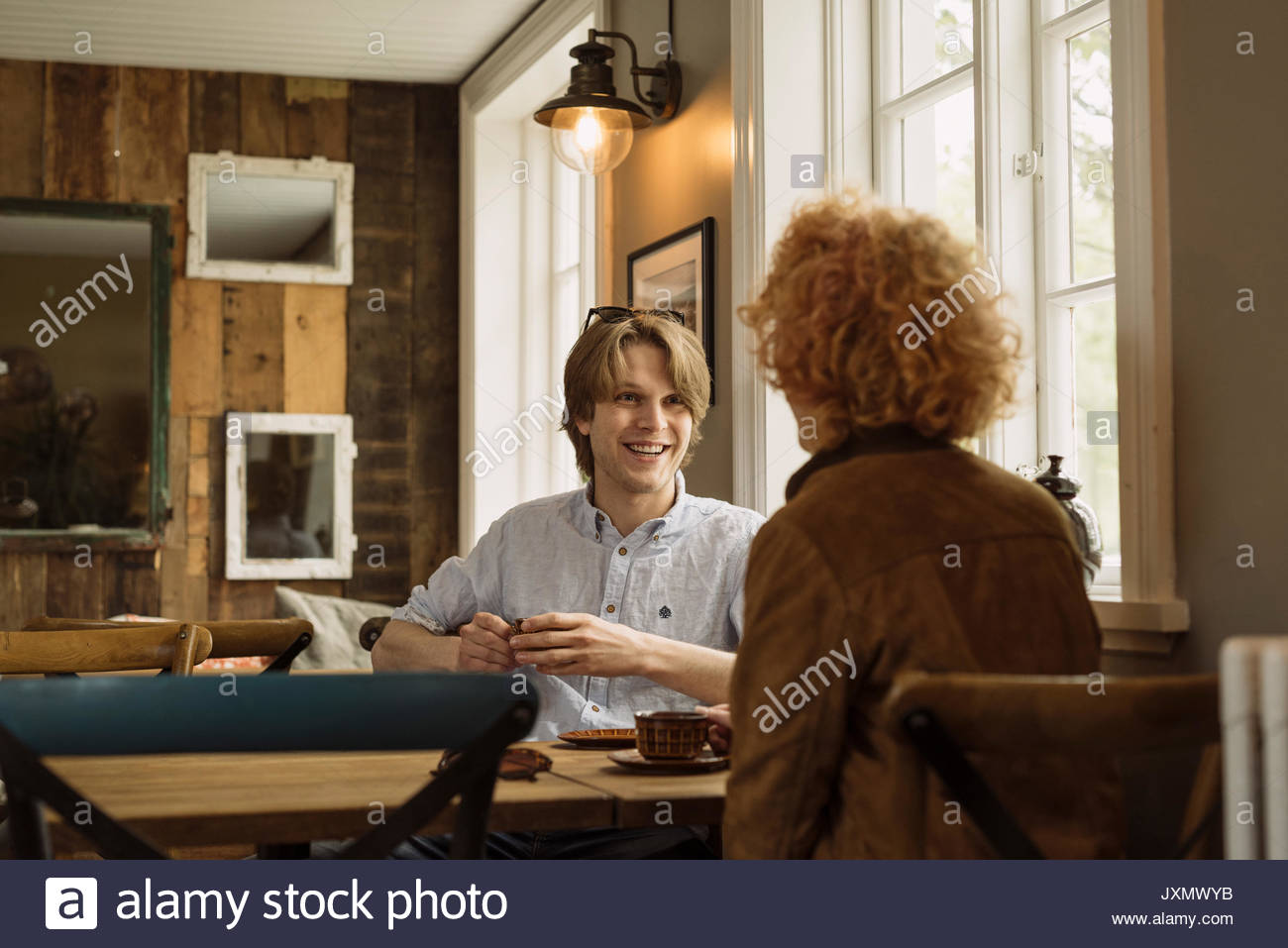 Couple on date in cafe smiling - Stock Image