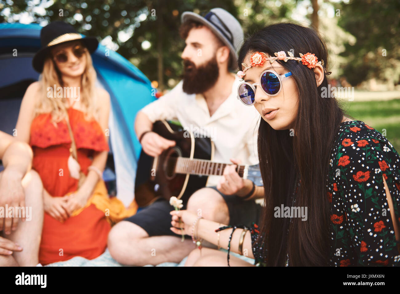Young boho adults playing acoustic guitar at festival - Stock Image