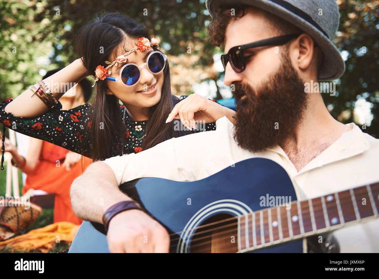 Young boho couple playing acoustic guitar at festival - Stock Image