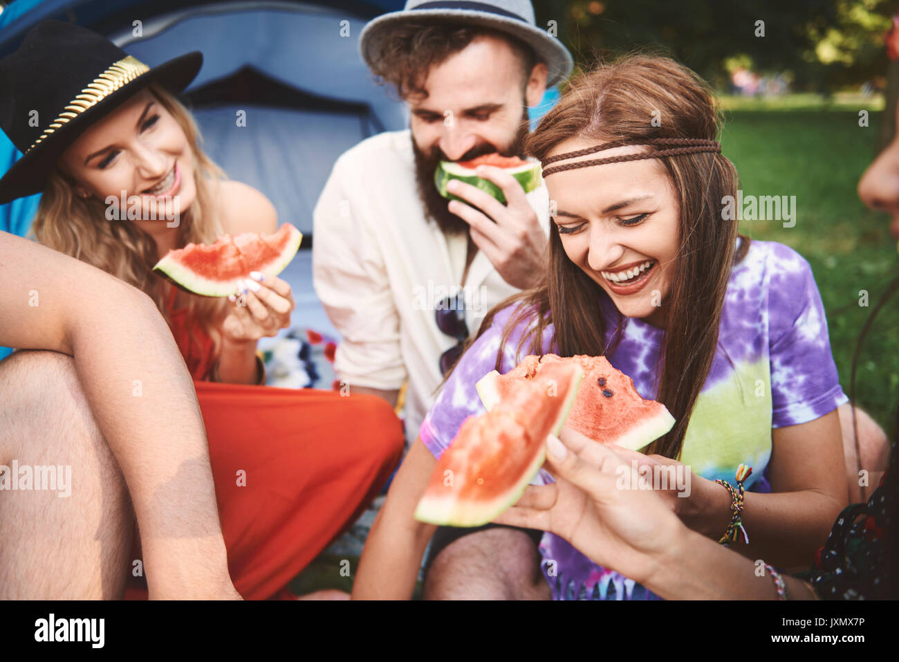 Young boho adult friends eating melon slices at festival - Stock Image