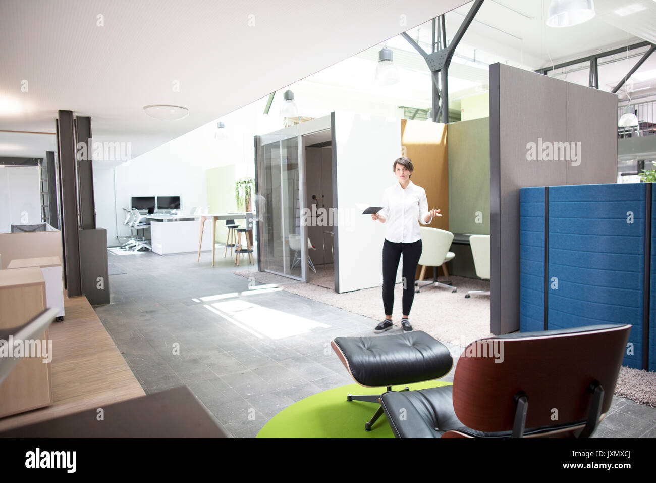 Portrait Of Young Female Sales Manager Giving Presentation In Office  Furniture Store