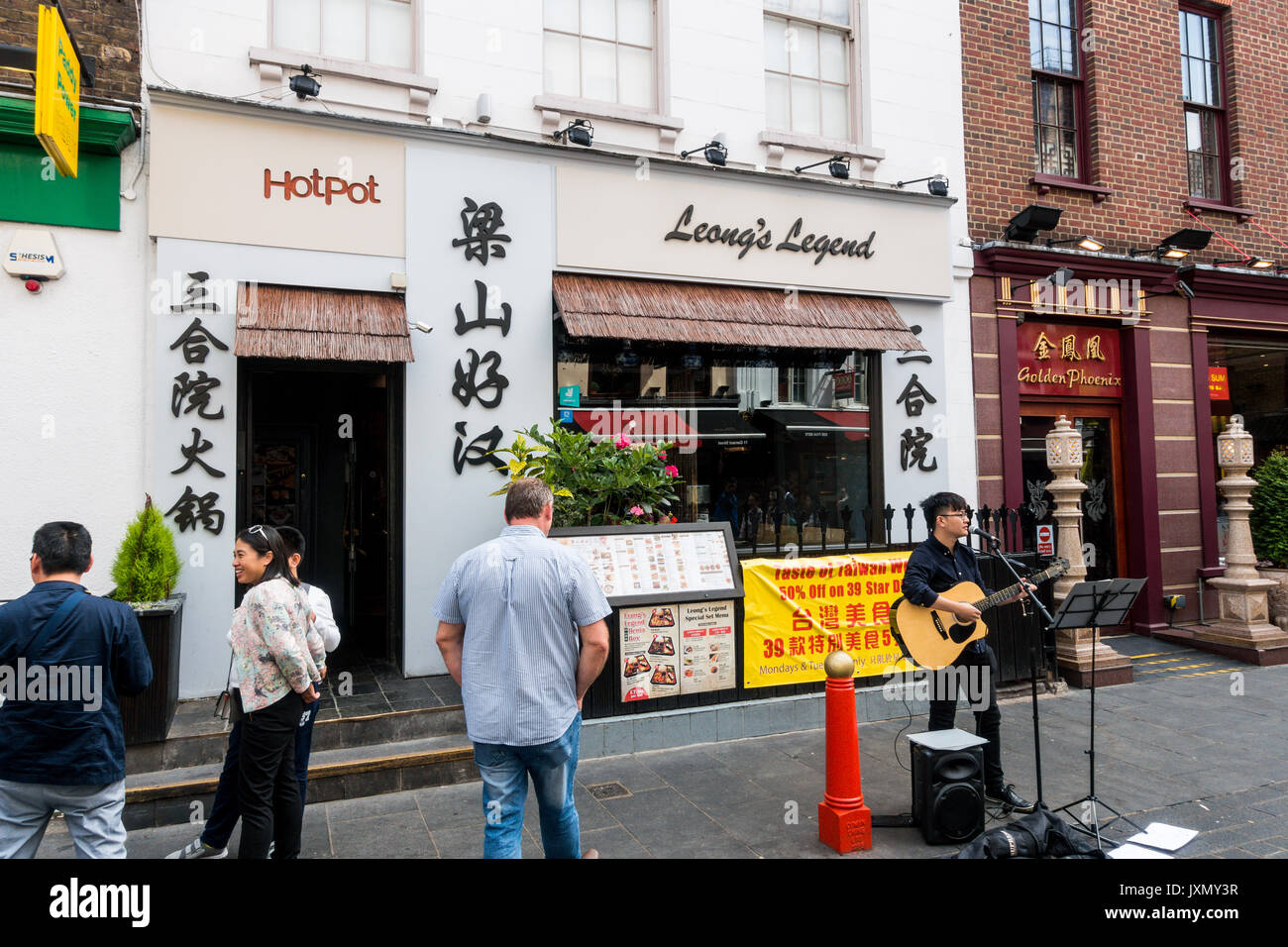 Chinese guitar vocalist outside leong's legend, chinese restaurant, chinatown, London - Stock Image