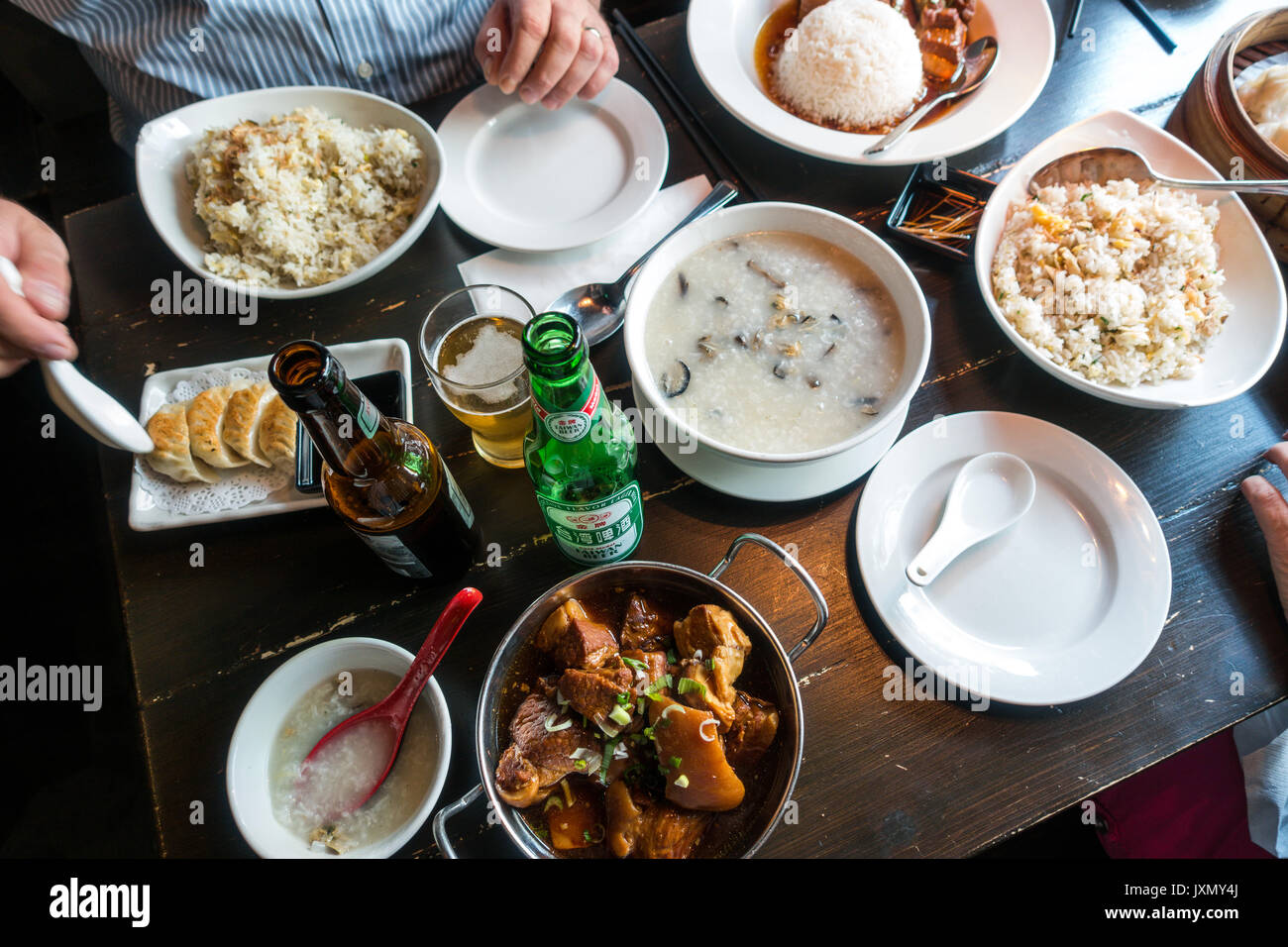 Leongs legend, Chinatown, London, multiple dishes on the lunchtime table including beer, oyster congee ,fried rice, pork bellies, chicken dumpling - Stock Image