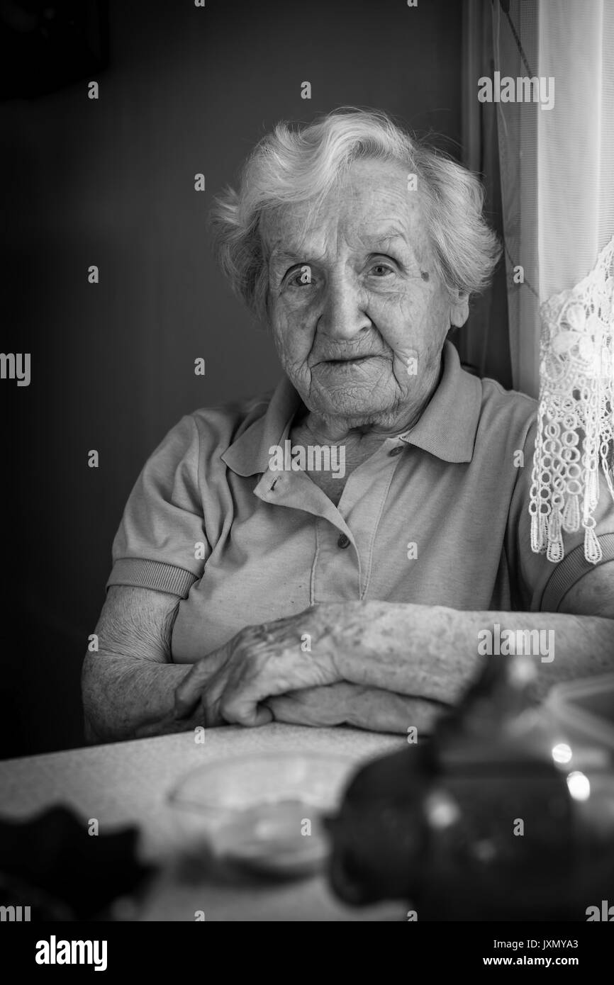 Monochrome portrait of elderly woman sitting at the table. - Stock Image