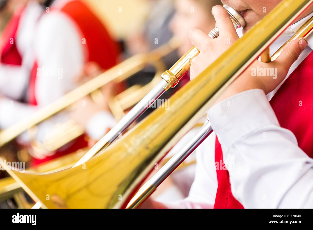 musical instrument, brass band and celebration concept - closeup playing trombone with mouthpiece and male hands, holiday performance of musicians in red and white concert suits, selective focus. - Stock Image