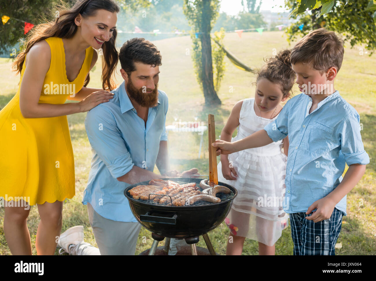 Father and son preparing meat on charcoal barbecue grill during  - Stock Image
