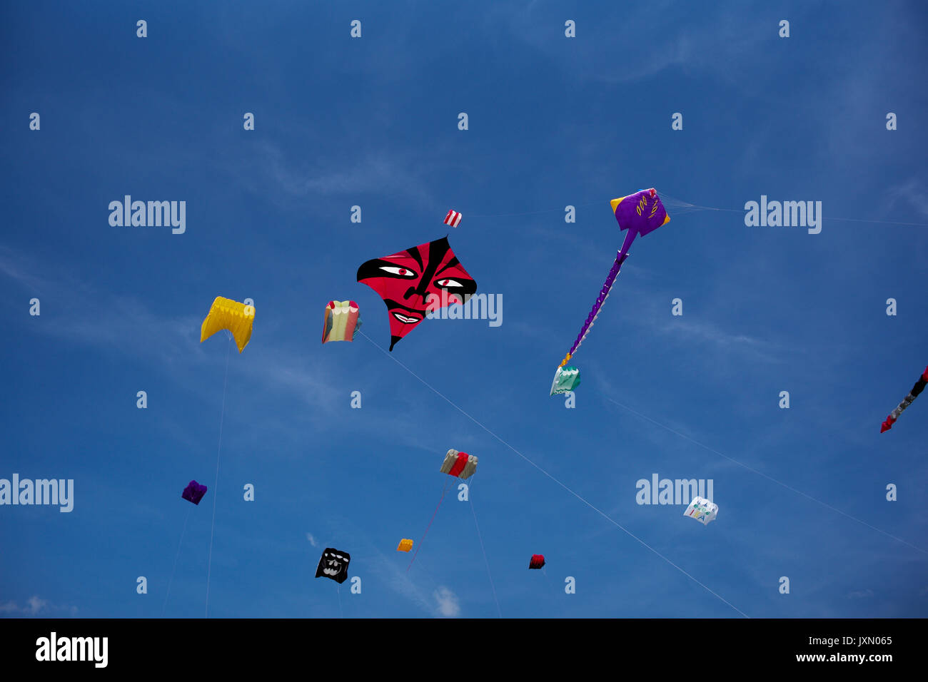 kites flying against a blue sky with one having a distinctive scary face Stock Photo
