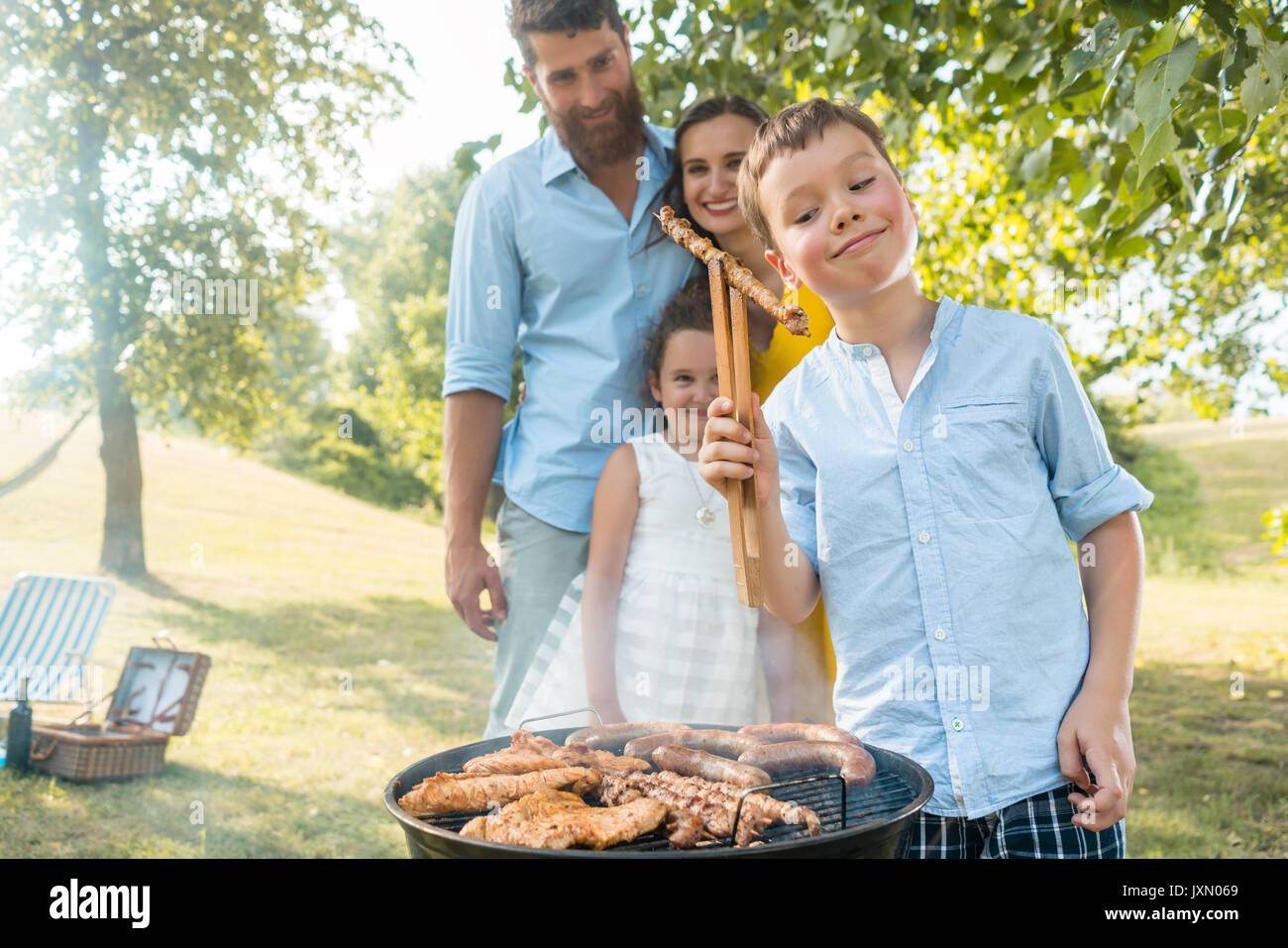 Portrait of happy family with two children standing outdoors nea - Stock Image