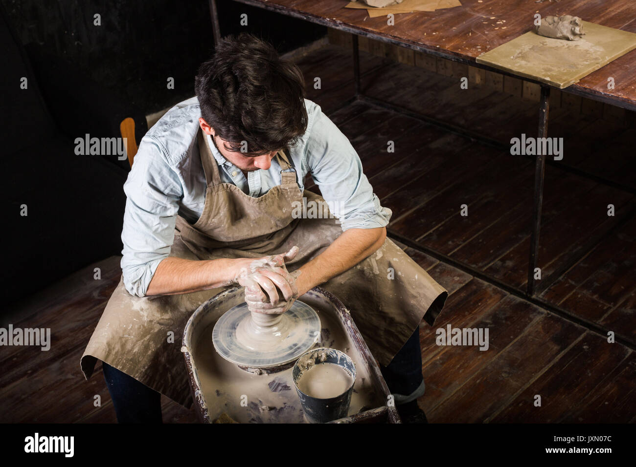 pottery, workshop, ceramics art concept - master forms the clay on Potter's wheel with hands, man bent over the work, a male sculpts a utensil near wooden table, man in apron and shirt, top view. - Stock Image