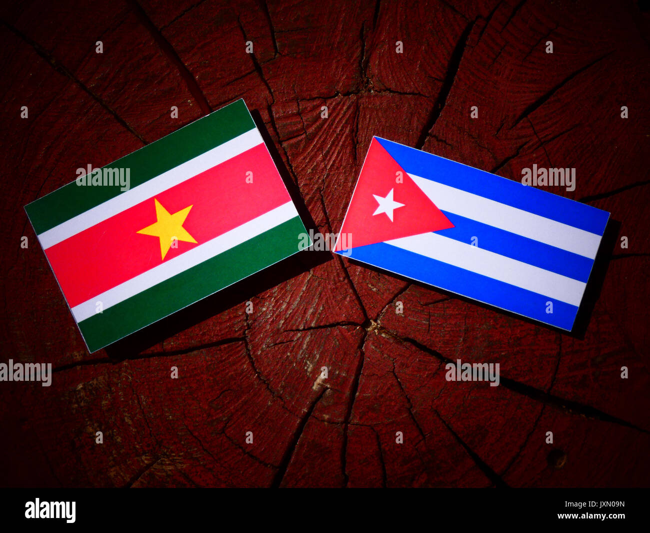 Suriname flag with Cuban flag on a tree stump isolated - Stock Image