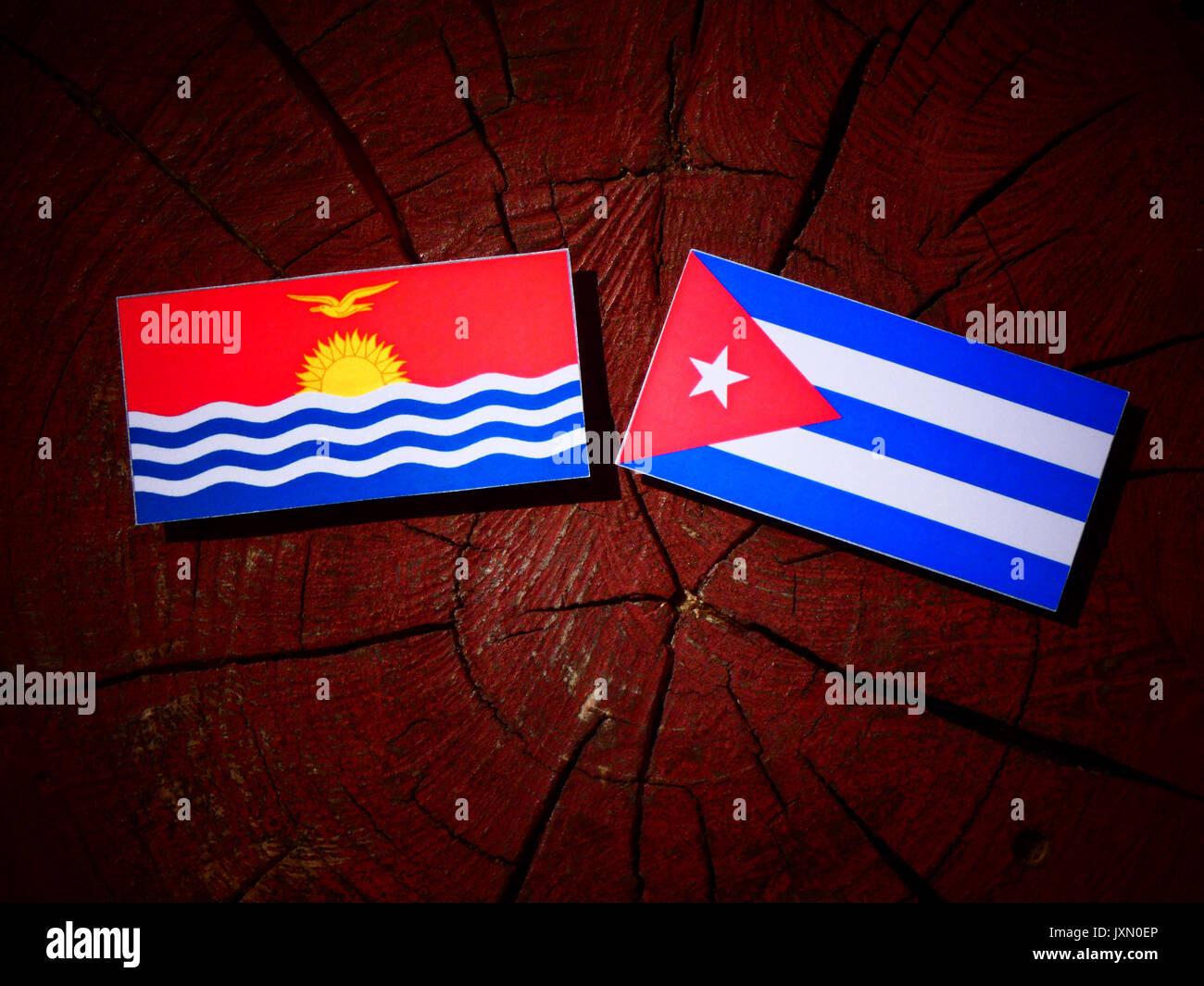 Kiribati flag with Cuban flag on a tree stump isolated - Stock Image
