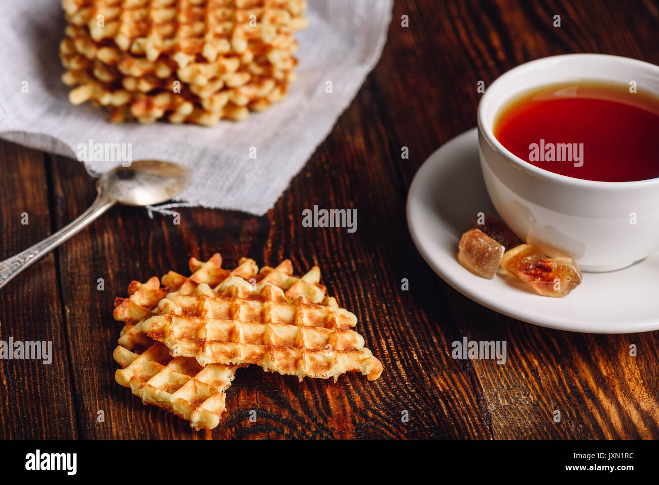 White Cup of Tea with Waffles Stack on Napkin and Pieces of Waffle on Wooden Surface and Spoon. - Stock Image