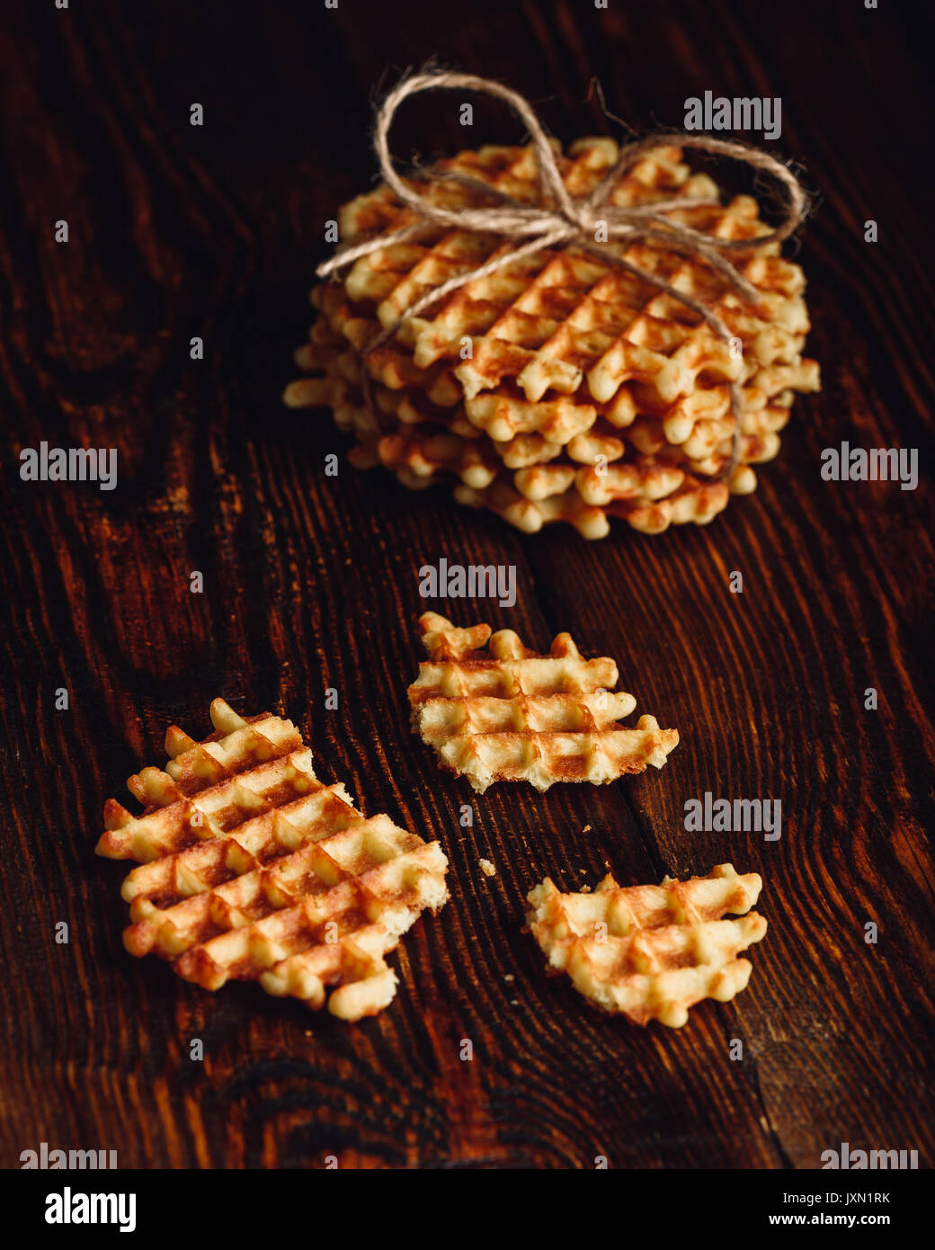 Stack of Belgian Waffles and Waffle Pieces on Wooden Surface. Vertical Orientation. - Stock Image