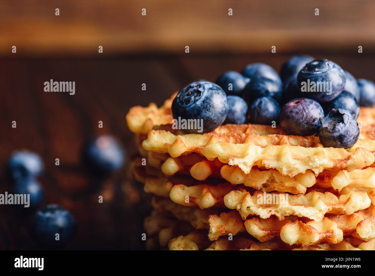 Blueberries on the Top of the Waffles Stack and Other Scattered on Wooden Background. - Stock Image