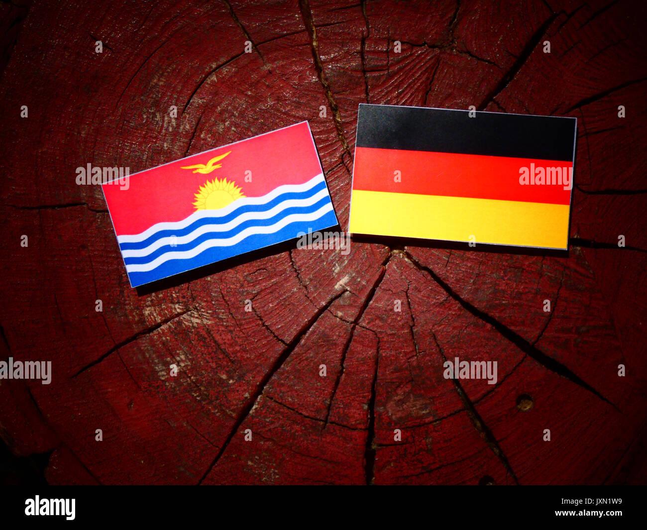 Kiribati flag with German flag on a tree stump isolated Stock Photo
