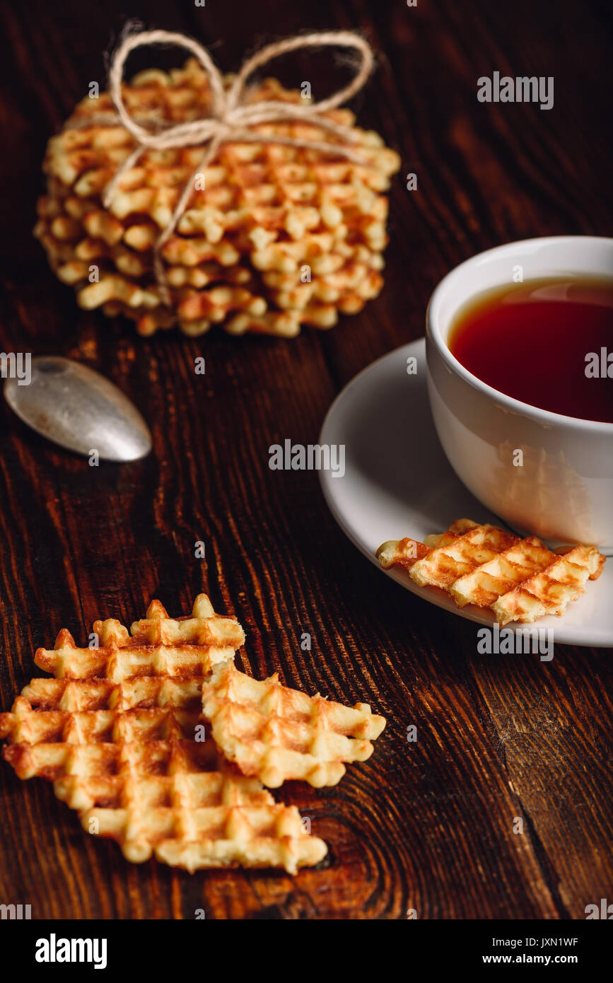 Waffles Pieces with White Cup of Tea and Stack of Waffles on Backdrop. - Stock Image